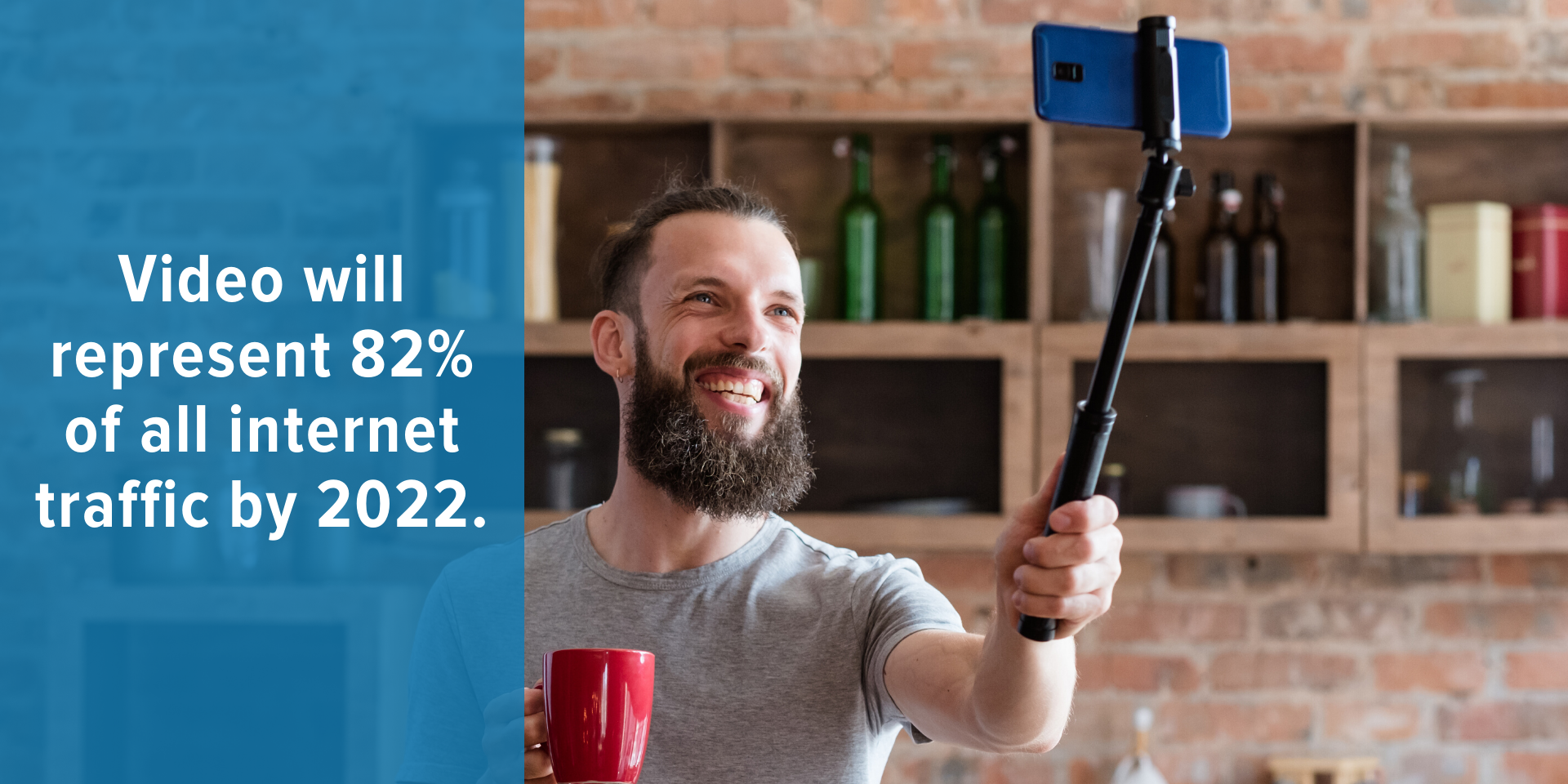 Man holding phone on a selfie stick taking a personal video in his kitchen to share as part of his marketing plan
